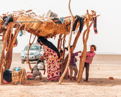 A nomadic family playing in the Sahara Desert while their mother prepares us some mint tea