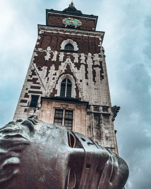 The Town Hall Tower and a sculpture of a head in the old town of Krakow, Poland