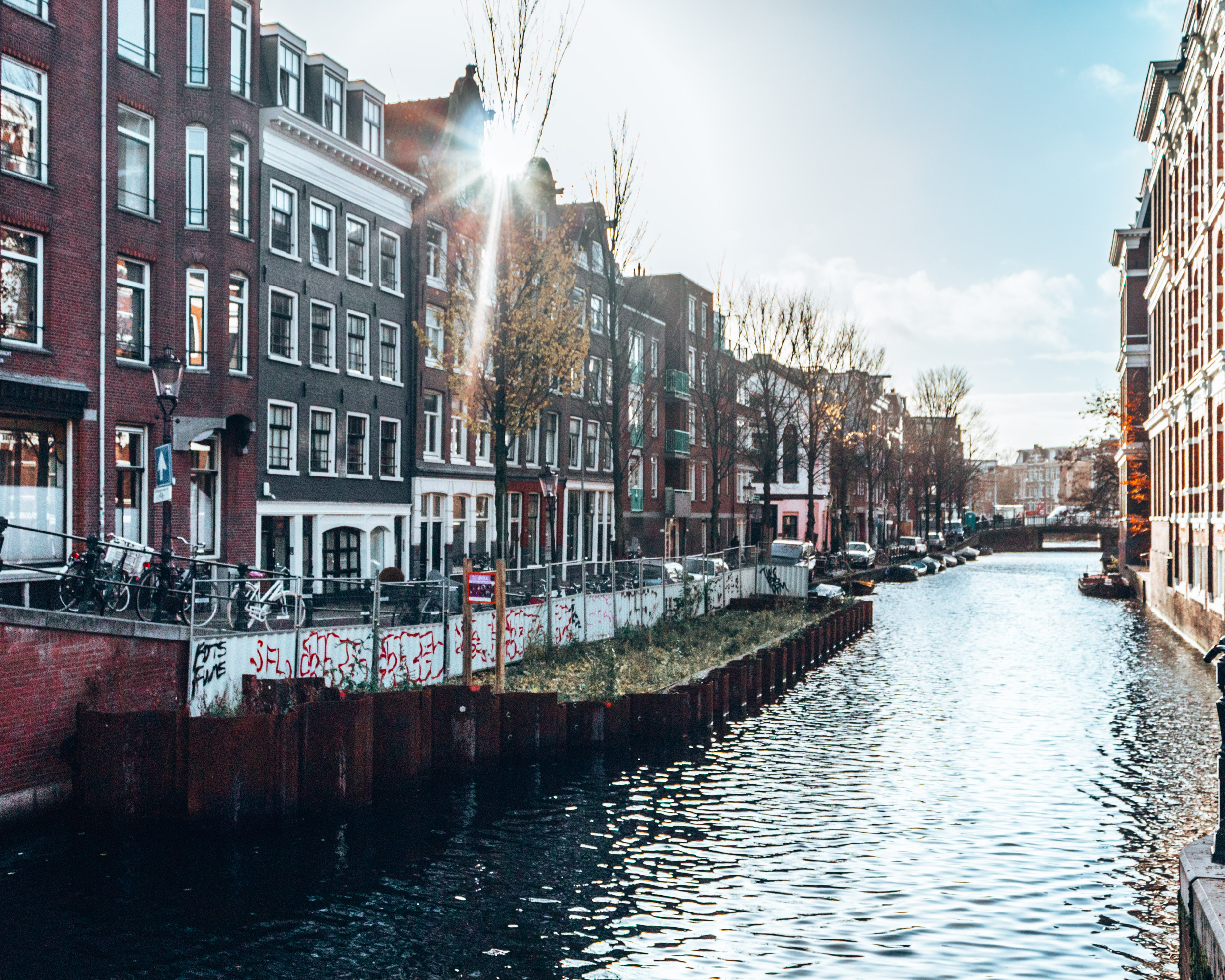 The sun peaking over the buildings by the canals in Amsterdam, Netherlands