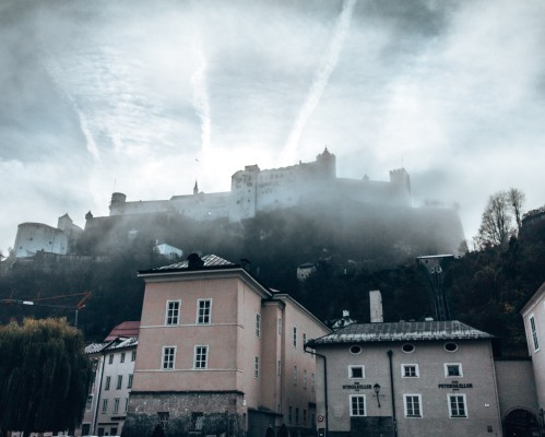 The Hohensalzburg Fortress seen through the early morning fog in Salzburg, Austria